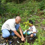 Leonard Bisel shows Christopher how to pat down the soil around the seedling.