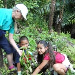 Teacher Sunny Seal-Laplante and students Dylan and Lei Meisha plant a seedling.